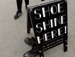 A a sign for 'Shoe Shine Here' near the Dr Martins shop.