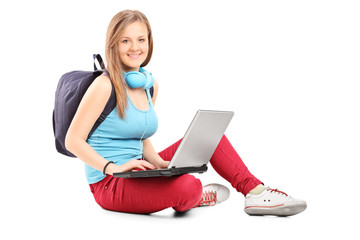 Female student working on laptop seated on ground