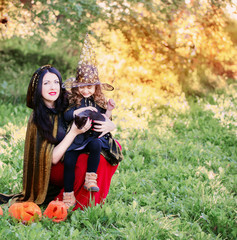 mother and daughter with pumpkins dressed as witches outdoor