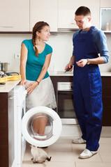 Housewife watching as engineer  repairing washing machine
