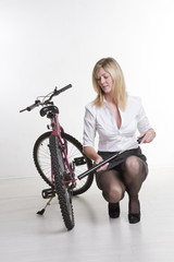 Woman inflating the tyre of her bicycle