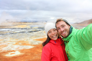 Iceland tourists selfie at mudpot hot spring