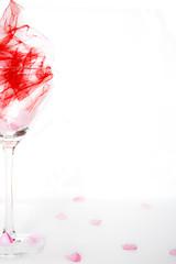 Bicchiere cocktail su sfondo bianco con petali rosa