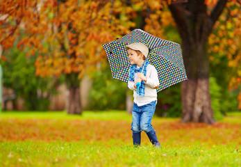 happy boy enjoying an autumn rain in park