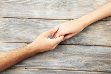 Loving couple holding hands close-up on wooden background