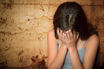 Teenage girl crying sitting on the floor