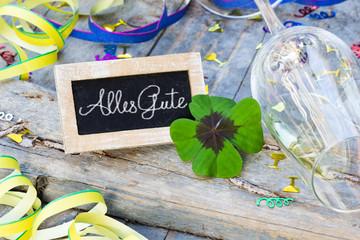 Partydekoration und Tafel mit Kleeblatt auf Holz, Alles Gute