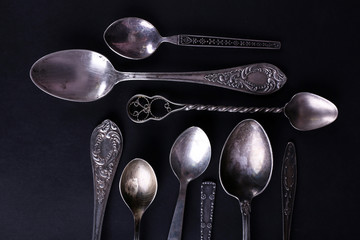 Metal spoons on black background