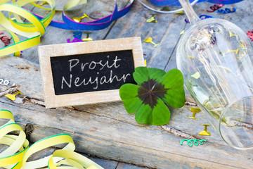 Partydekoration und Tafel mit Kleeblatt auf Holz, Prosit Neujahr