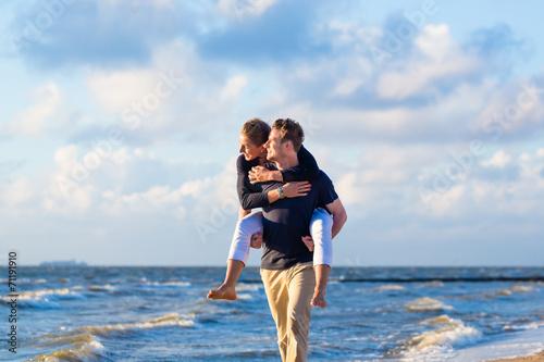 canvas print picture Mann trägt Frau huckepack am Strand