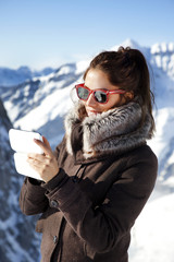 young woman with smartphone at the Alps