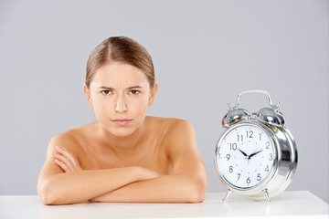 Woman with Arms Crossed Next to Alarm Clock