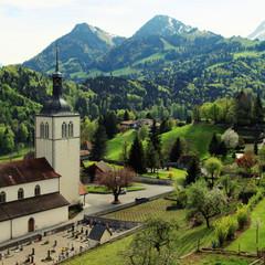 Church and Alps mountains, Gruyeres, Switzerland