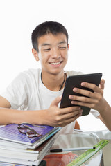 Asian teenager using his tablet or ipad and happy to find someth