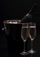 Bottle of champagne in bucket, two glasses