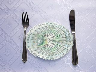 Eating polish money bill for dinner. Consumption.