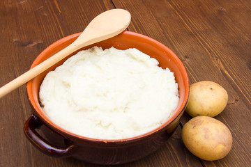 Mashed potato with spoon on wooden table