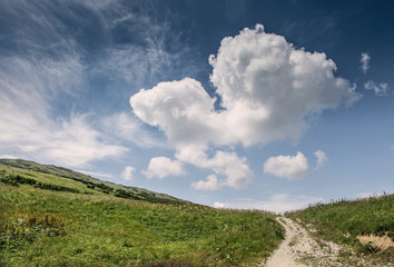 Hill landscape with deep blue sky and big cloud