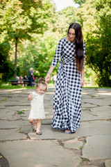 young brunette woman walking with baby girl at park