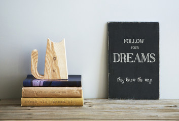 motivational quote  FOLLOW YOUR DREAMS on chalkboard with books