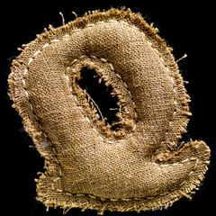 Linen or hemp vintage cloth letter Q isolated on black