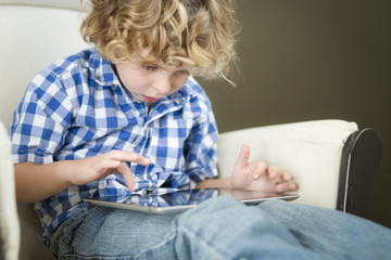 Young Blond Boy Using His Computer Tablet