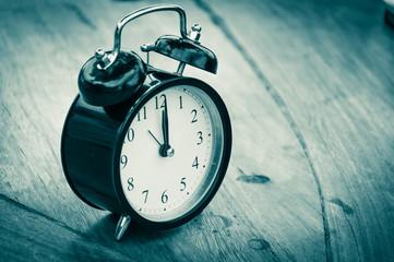 Retro alarm clock on a wood table. Photo in retro color image st