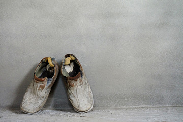 A pair of old shoes on cement background, old background