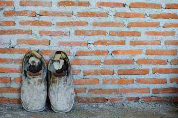 A pair of old shoes on brick wall background, old background
