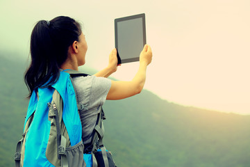 woman hiker on mountain taking photo with digital tablet