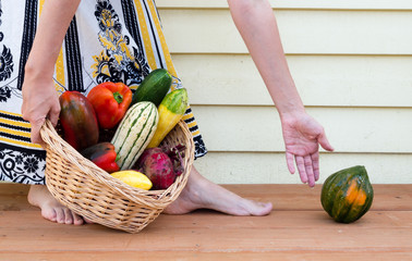 Woman with veggie basket catching a fallen squash