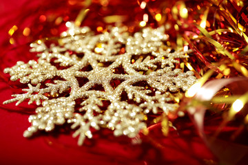 Golden snowflake and tinsel close-up on red christmas background