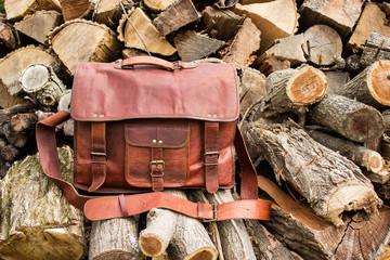 Vintage look handmade leather bag on a wood pile