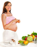 Pregnant woman eating vegetable.