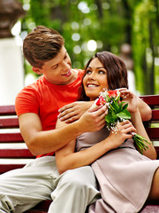 Couple with flower at park.