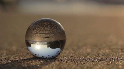 Glass sphere on a sandy beach