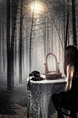 Possessed girl sitting in a haunted forest in front of a mirror
