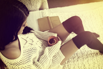 Girl in stockings rests with hot tea