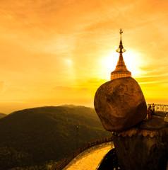 Kyaikhtiyo pagoda or Golden rock with sunset sky in Myanmar