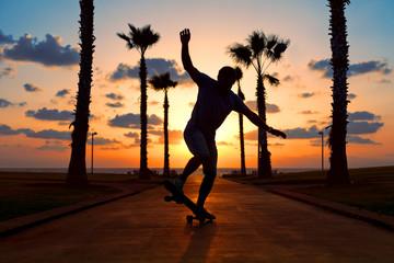 man riding on skateboard near the ocean in sunset