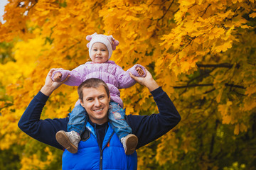 happy father with a toddler in the autumn park