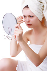 young girl in a towel on his head, sees his face in the mirror.