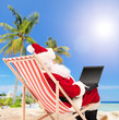 Santa playing with laptop on a beach
