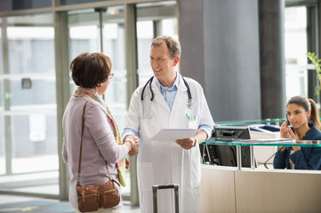 Male doctor shaking hands with his patient at hospital reception desk