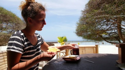 Young Woman Having Breakfast by the Sea on the Beach.