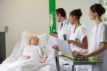 Medical team discussing female patient record in hospital bed