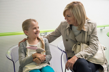 Woman with her daughter sitting in hospital waiting room