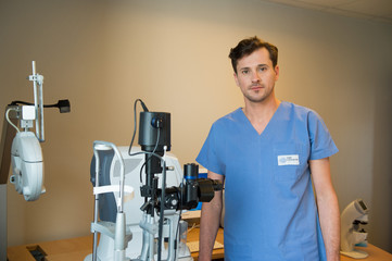 Male doctor with eye test equipment