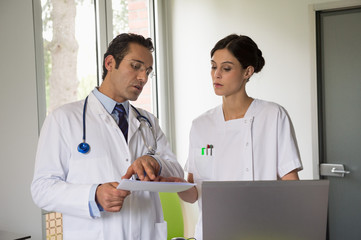 Doctor giving instructions to female nurse in hospital