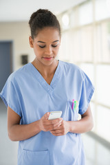 Female nurse text messaging with a mobile phone